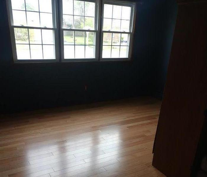 Clean room with new hardwood floors, three windows in background