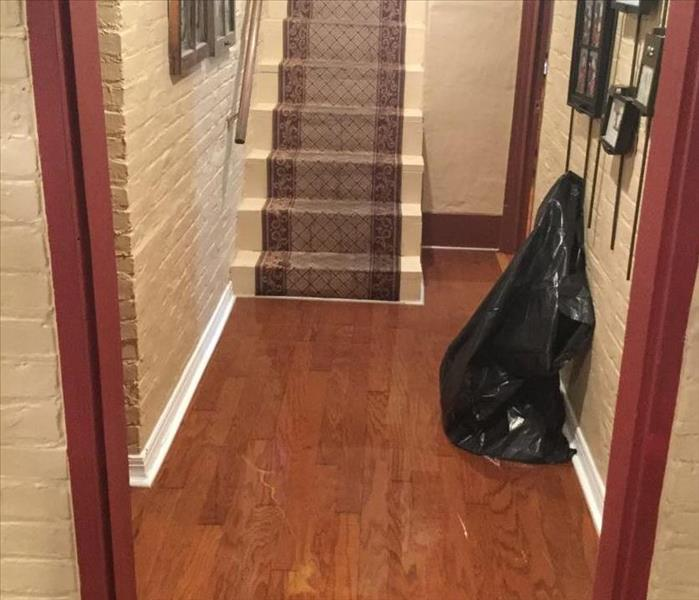 Hallway in a basement, stairs in background, hardwood floors covered with water.